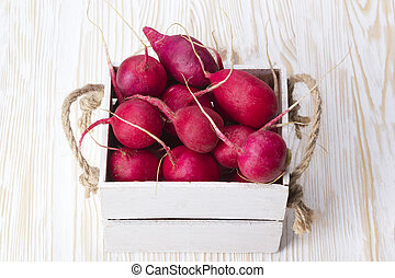 Red radishes in a wooden box.