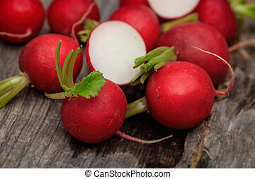 Red radishes some cut in two, on wooden surface