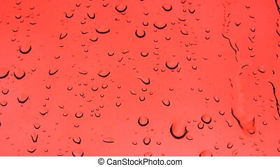 Red abstract background with rain drops on the window glass