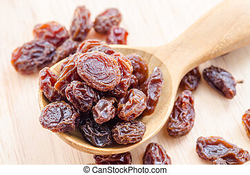 Red raisins in a wooden spoon.