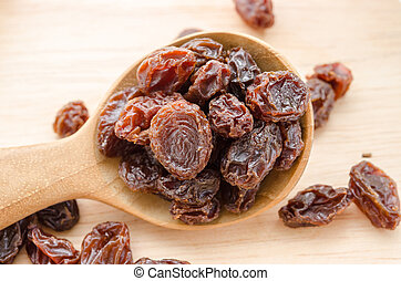 Red raisins in wooden spoon
