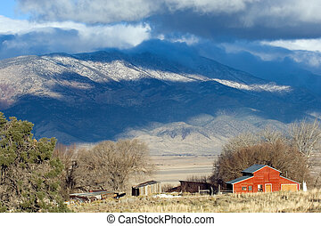 Red ranch house in Nevada state with mountain range on background