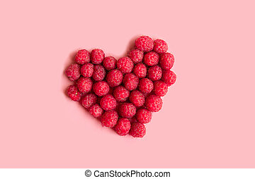 Red raspberries in a heart shape on pink background