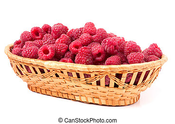 red raspberries in a wicker basket isolated