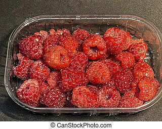 Red raspberries in plastic package / box on the brown wooden table