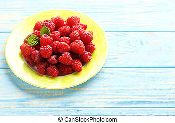 Red raspberries in plate on a blue wooden table