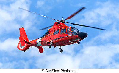 Red rescue helicopter moving in blue sky