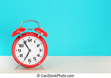 Red retro alarm clock with five minutes to seven o'clock, on wooden table on a blue background