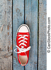 Red retro sneakers on a blue wooden background