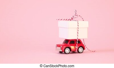 Red retro toy car delivery gift box with ribbon bow on a pink background. Birthday, Valentine's Day, Women's Day video concept.