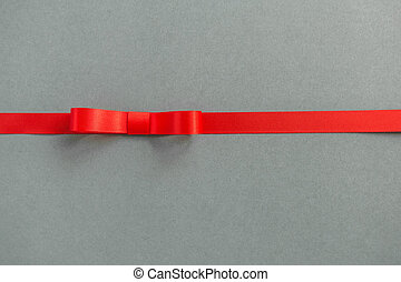 Red ribbon and bow with soft shadow on gray background