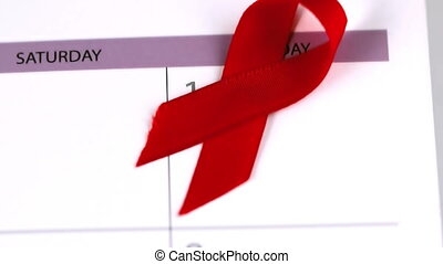 Red ribbon falling on a calendar