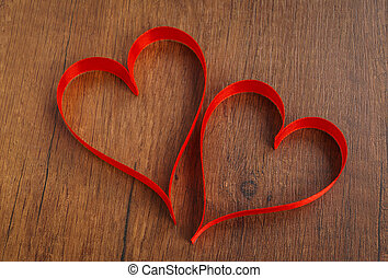 Red ribbon hearts on wood background For Valentines day
