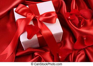 Red ribbon holiday gift on satin