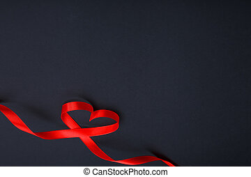 red ribbon in the shape of a heart on a black
