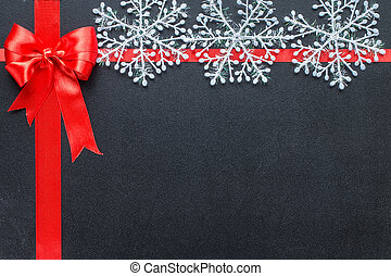 Red ribbon on a black chalkboard with snowflakes