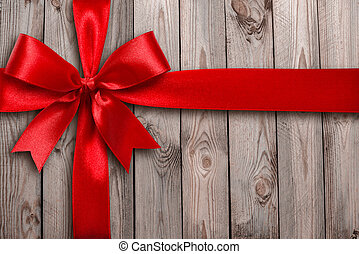 Red ribbon on a wooden background