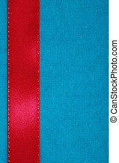 red ribbon on blue fabric background with copy space.