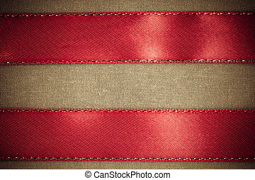 red ribbon on brown fabric background with copy space.