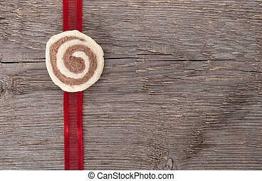 red ribbon with a cookie on wood with copy space as...