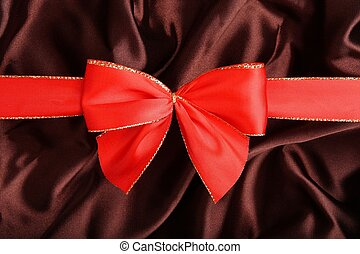 Red ribbon with brown smooth textile- background