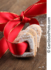 Red ribbon with shortbread hearts. Shallow dof