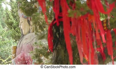 Red ribbon wrapped around branches.China Fortuna sculpture...