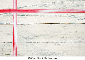 Red ribbons on a white wooden background