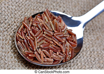 Red rice in a spoon