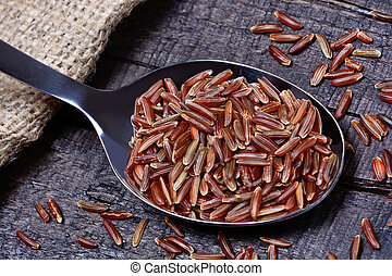 Red rice in a spoon on table