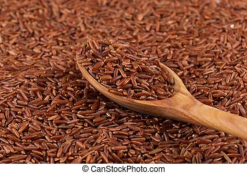 Red rice in a wooden spoon