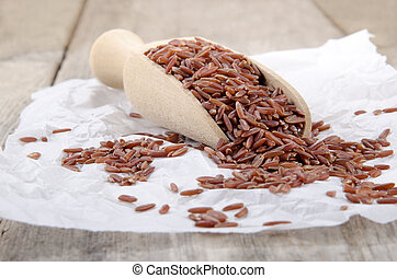 red rice on a wooden shovel with white paper