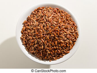 Red Rice seed. Top view of grains in a bowl. White background.