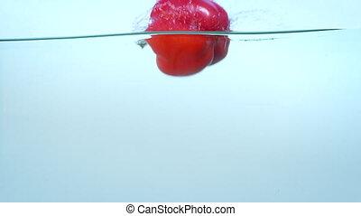 Red ripe bell pepper in water in slow motion