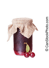 Red ripe cherries and a glass jar with cherry jam