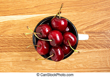 Red ripe cherries in a white iron mug in the center of a wooden background