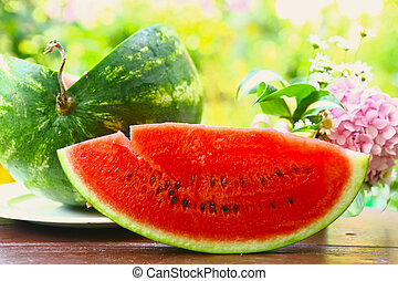 red ripe cut water melon with hydrangea bouquet close up photo on summer sunny garden background