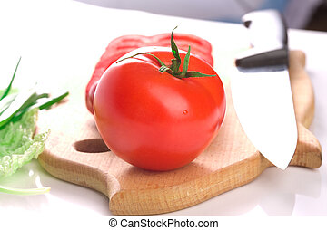 Red ripe fresh tomato on cutting board with knife