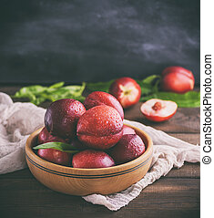 red ripe peaches nectarine in a brown wooden bowl on a...