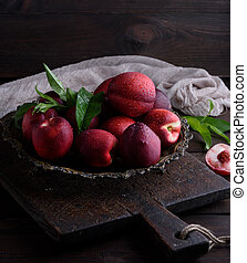 red ripe peaches nectarine in an iron plate, close up
