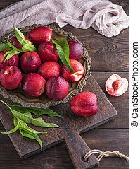 red ripe peaches nectarine in an iron plate on a brown...