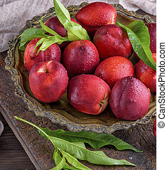 red ripe peaches nectarine in an iron plate, top view, close...