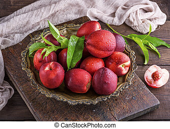 red ripe peaches nectarine in an iron plate, top view