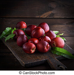 red ripe peaches nectarine on a brown wooden board, copy...