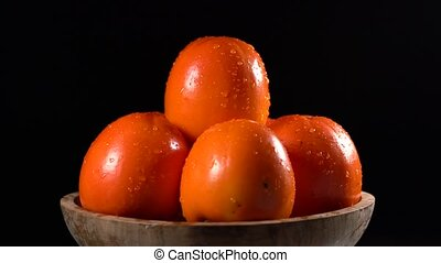 Red ripe persimmons rotating over black background, seamless...