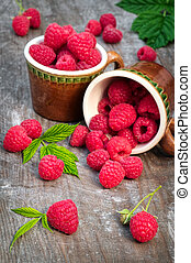 Red ripe raspberries on a wooden background