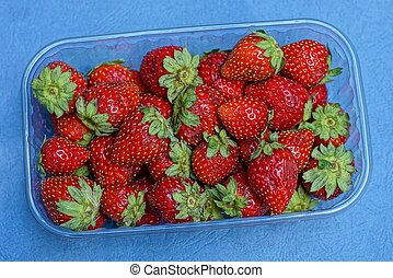 red ripe strawberries in a plastic box