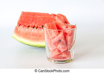 Red ripe watermelon, sliced on a white background. Watermelon slices in a glass.