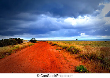 Red road to sea under the cloudy sky