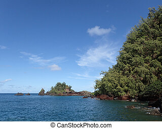 Red Rock cliff and islands covered with trees along the ocean